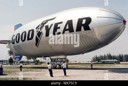 The ground crew is ready for the Goodyear blimp 'Mayflower' to rise from its East Coast operations base in Miami, Florida, USA, in 1976. The Mayflower was later replaced by the 'Spirit of Innovation,' one of three Goodyear blimps in the U.S. that flew as iconic airborne advertisements for the tire and rubber company. By early 2017, Goodyear had replaced all three of those non-rigid air-bag vehicles with German-built Zeppelins that have rigid internal structures. The airships are most frequently seen hovering above sporting events to provide aerial coverage on television. Historical photo. - Stock Photo