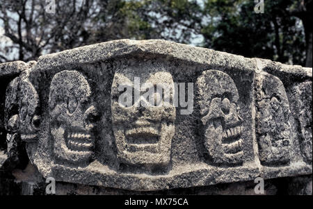 This is a close-up of the human skulls carved in stone by Mayans on a corner of the Tzompantli ruin at the ancient archaeological site of Chichen Itza on the Yucatan Peninsula in Mexico. Better known as the Wall of Skulls or the Skull Platform (Plataforma de los Cráneos), this was the public place for carrying out human sacrifices and also displaying the heads of dead enemies as a warning to potential invaders. Chichen Itza was one of the largest Maya cities in pre-Columbian times and is now a UNESCO World Heritage Site and major Mexican tourist attraction. Historical photograph. - Stock Photo