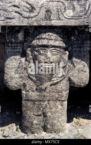 This is a close-up of one of the ancient stone statues carved by Mayans that hold up an altar in the Temple of the Warriors at the archaeological site of Chichen Itza on the Yucatan Peninsula in Mexico. Chichen Itza was one of the largest Maya cities in pre-Columbian times and is now a UNESCO World Heritage Site and major Mexican tourist attraction. Historical photograph. - Stock Photo