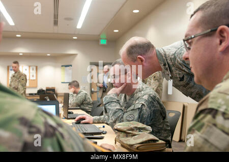 Maj. Gen. Don Dunbar watches the screen of a cyber forensics trainee during the Cyber Shield 17 exercise at Camp Williams, Utah, May 3, 2017.  Cyber Shield is a National Guard exercise designed to assess Soldiers, Airmen and civilian personnel on response plans to cyber incidents taking place April 24 to May 5, 2017 at Camp Williams, Utah. (Wisconsin Army National Guard : Staff Sgt. Matthew Ard) - Stock Photo