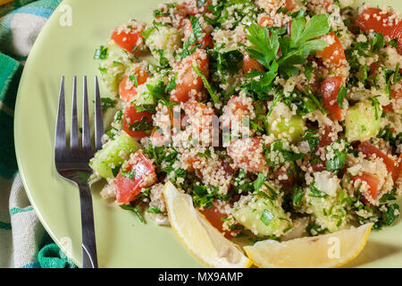 Tabbouleh salad with couscous in green plate on rustic table - Stock Photo
