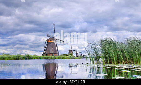 Windmills with dramatic shaped clouds reflected in a canal, Kinderdijk, The Netherlands - Stock Photo