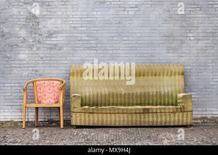 Old worn-out furniture against ta great brick wall, Beijing, China - Stock Photo