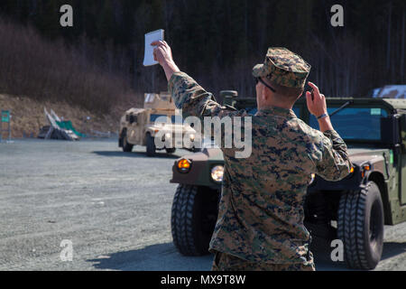 U.S. Marine Corps Cpl. Buck Ems, a Landing Support Specialist with 2nd Transportation Support Battalion, guides Humvees to park in the assembly area following a convoy at Strategic Mobility Exercise 17 (STRATMOBEX) near Stjørdal, Norway, May 3, 2017. During this exercise Marines pulled vehicles from caves of the Marine Corps Prepositioning Program in Norway (MCPP-N). MCPP-N provides an alternative to shipping equipment from the United States in order to decrease operation response times. - Stock Photo