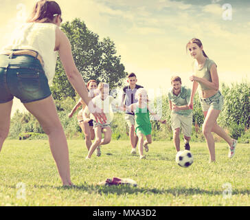 Smiling family with four kids playfully running after ball outdoors on green lawn in park. Focus on teenager girl - Stock Photo