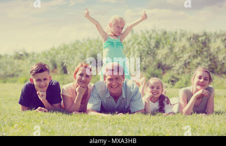 happy smiling mature couple with four different age children lying on the grass in park on summer day - Stock Photo