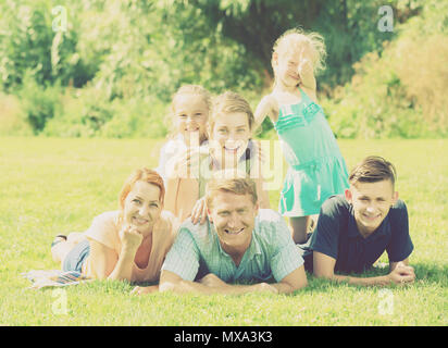 Young man and woman with kids lying in park on summer day - Stock Photo