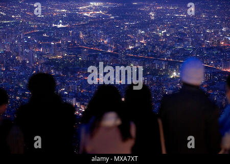 Cityscape of Sapporo with city lights at night in focus and out-of-focus people in the foreground. In Sapporo, Hokkaido, Japan. - Stock Photo