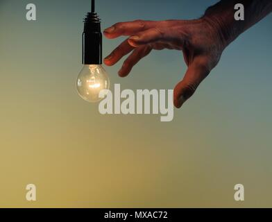 Incandescent light bulb with male hand on a blue and yellow background. - Stock Photo
