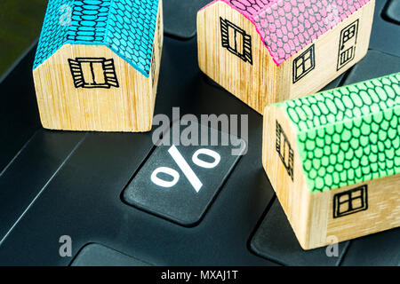 big black calculator with big percentage button and three miniature wooden houses - Stock Photo