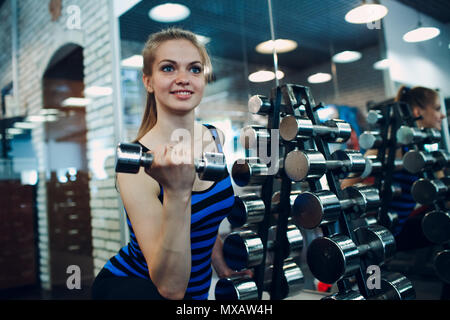 Young woman exercising byceps. Close up portrait image of attractive fit woman in fitness gym. - Stock Photo
