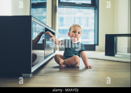 A little baby is cruising on the furniture by the television - Stock Photo