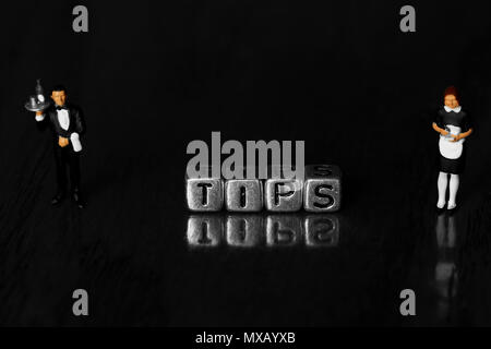 Tips on beads with a scale model waiter and waitress standing next to word on wooden background - Stock Photo