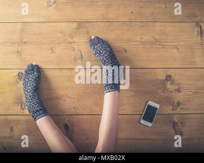 Overhead shot of a woman's feet in worn socks on the floor with a cracked smart phone - Stock Photo