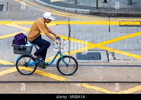 Chinese man on bicycle in Central, Hong Kong, SAR, China - Stock Photo