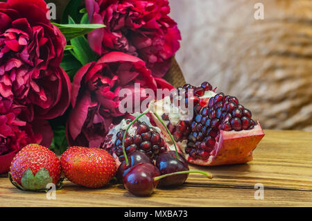 Still life in red tones. Peonies, pomegranate, cherry and strawberry. On a wooden table. - Stock Photo