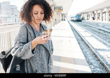 Young black woman waiting for the train on station platform - Stock Photo