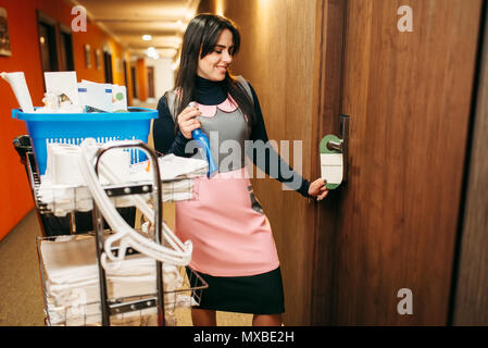 Housemaid in uniform finished cleaning the room, corridor of hotel on background. Professional housekeeping, charwoman - Stock Photo