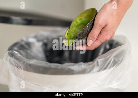 Woman dumping organic trash into the garbage can. - Stock Photo