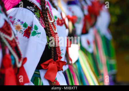 Regional, folklore costumes, colorful handmade shirts with symbols embroidered and necklaces During Corpus Christi parade. - Stock Photo