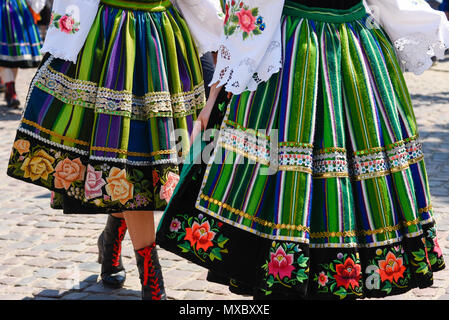 Regional, folklore costumes, colorful handmade skirts with stripes and symbols embroidered. During Corpus Christi parade. - Stock Photo