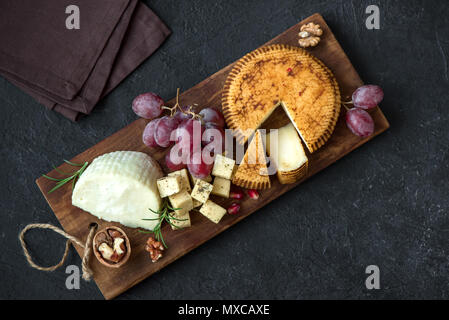 Cheese platter with assorted cheeses, grapes, nuts over black background, copy space. Italian cheese and fruit platter. - Stock Photo