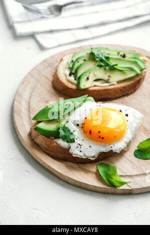 Avocado Sandwich with Fried Egg - sliced avocado and egg on toasted bread for healthy breakfast or snack, copy space. - Stock Photo