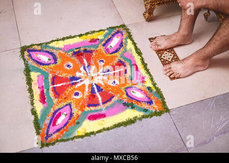 The feet of the groom infront of the traditional rangoli art decoration from the multi-color rice and sand during the traditional indian ceremony vefo - Stock Photo