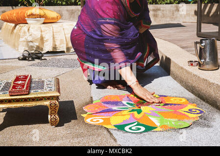 Women decorating and coloring tradition colorful rice art or sand art (Rangoli) on the floor with paper pattern using dry rice and dry flour with colo - Stock Photo
