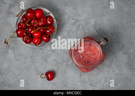 cherry smoothie in Mason jar on a gray concrete background. view from above - Stock Photo