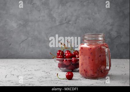 cherry smoothie in Mason jar on a gray concrete background - Stock Photo