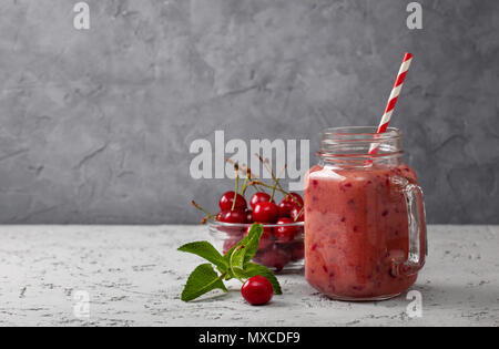 cherry smoothie in Mason jar on a gray concrete background - Stock Photo