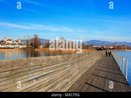 Rapperswil, Switzerland - November 30, 2016: wooden pedestrian bridge over Lake Zurich between the town of Rapperswil and the village of Hurden, which - Stock Photo