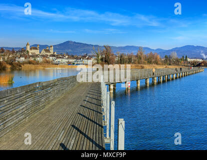 Rapperswil, Switzerland - November 30, 2016: wooden pedestrian bridge over Lake Zurich between the town of Rapperswil and the village of Hurden - the  - Stock Photo