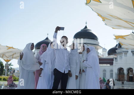 Banda Aceh, Aceh Province / Indonesia - June 3 2018 :Tourists are taking pictures/selfie in front of Baiturrahman grand mosque in Banda Aceh, Indonesi - Stock Photo