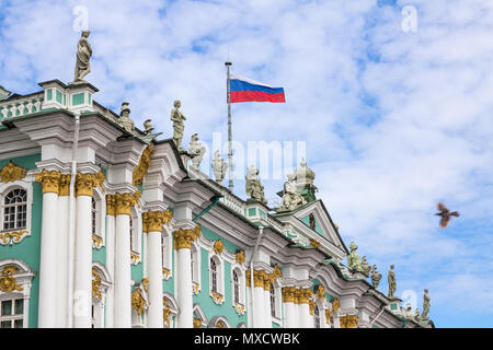 St Petersburg's beautiful Winter Palace painted mint green with white and gold trim. Statues line rooftop with Russian flag. Dove flies toward Palace - Stock Photo