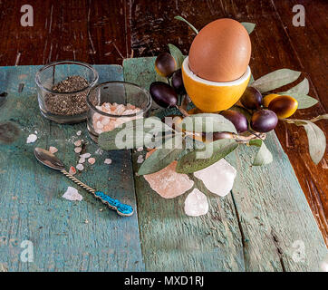 Single egg in a egg cup on a wooden surface with an assortment of crystal Hymalain pink salt and pepper. Olive decorative reef in the background. - Stock Photo