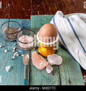 Single egg in a egg cup on a wooden surface with an assortment of crystal Himalayan pink salt and pepper. Stock Image - Stock Photo