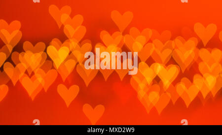 beautiful bokeh made of blurred lights in the form of hearts on red background - Stock Photo