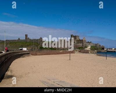 View along clean sandy beach towards impressive Peel Castle on St Patrick's Isle on a lovely May day Isle of Man - Stock Photo