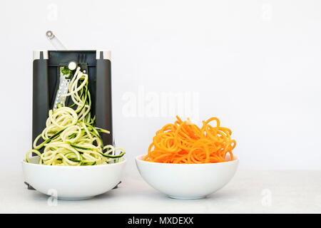 Spiralizing courgettes and carrots against a white background - Stock Photo