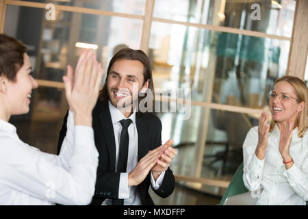Excited business partners applauding congratulating colleague wi - Stock Photo