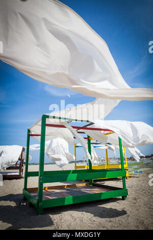 Sheds awning with white curtains on the seashore in the wind. - Stock Photo