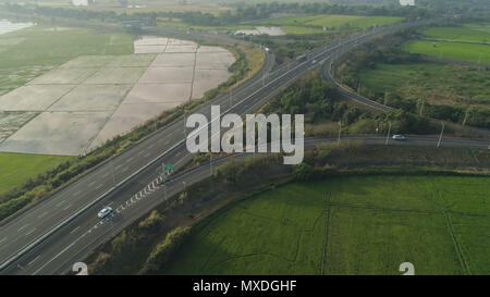Aerial view highway with cars among farmer fields, rice terraces. Philippines, Luzon. High speed highwayin the morning sunrise.Tropical landscape in Asia. - Stock Photo