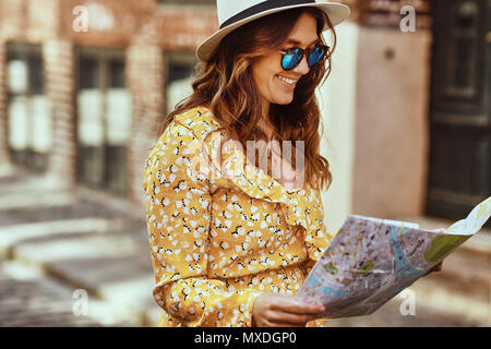 Smiling young brunette woman wearing a fedora and sunglasses exploring the cobblestone streets of a city with a map - Stock Photo