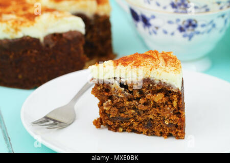 Slice of delicious carrot cake with marzipan icing on white plate - Stock Photo