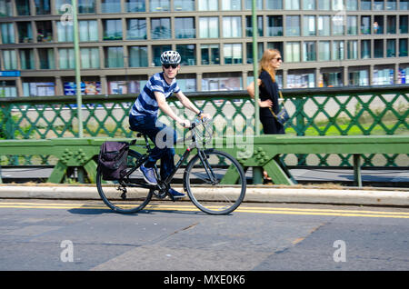 A man rides hi bicycle on the Hammersmith Bridge in London. - Stock Photo
