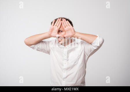 Young caucasian man hiding his face with hand - Stock Photo