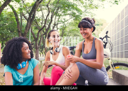 Group of sporty female friends bonding and laughing. Women hanging out and having fun while relaxing, resting after training. Trees in background. - Stock Photo