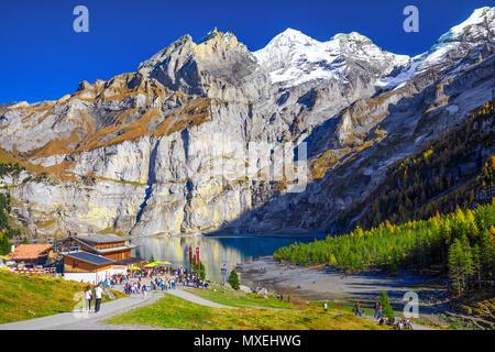OESCHINENSEE, SWITZERLAND - October 2017 - Amazing tourquise Oeschinnensee with waterfalls, wooden chalet and Swiss Alps, Berner Oberland, Switzerland - Stock Photo